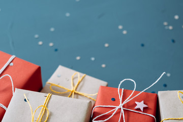 holiday season and christmas background. selection of presents in red and craft paper packaging on blue backdrop. copy space concept.