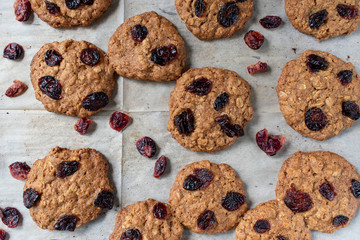 Homemade oatmeal cookies with dried cranberries on white baking parchment