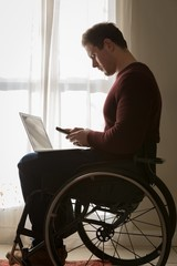 Disabled man using mobile phone at home