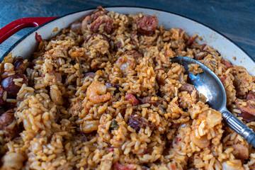 Baking dish with shrimp, sausage, and rice jambalaya and spoon