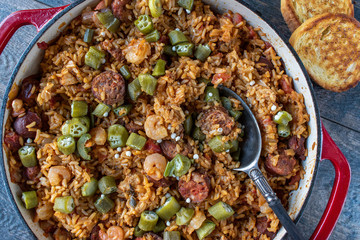 Baking dish with shrimp, sausage, and rice jambalaya and spoon