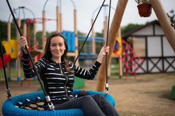 Portrait of a young woman swinging on a hanging swing smiling, concept of freedom, day off, remember childhood