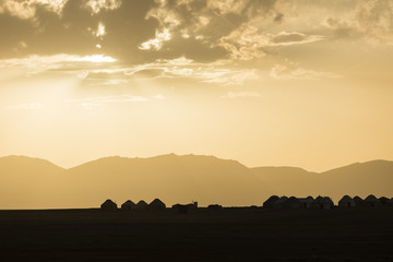 Silhouette of a yurt settlement at Song Kul lake in Kyrgyzstan at sunset
