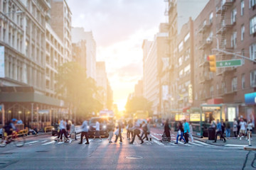 Diverse crowd of people walking across the busy intersection of 23rd Street and 6th Avenue in Manhattan New York City with the colorful light of sunset in the background