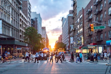 Fotomurales - Diverse crowd of people walking across the busy intersection of 23rd Street and 6th Avenue in Manhattan New York City with the colorful light of sunset in the background