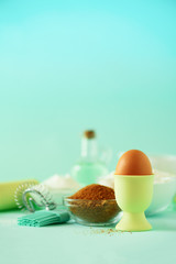 Time to bake. Baking ingredients - butter, sugar, flour, eggs, oil, spoon, rolling pin, brush, whisk, milk over blue background. Bakery food frame, cooking concept. Copy space