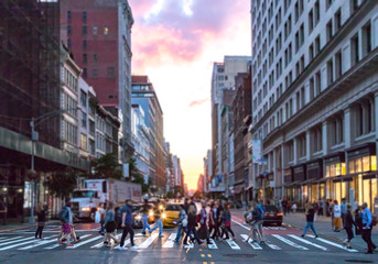 Diverse group of people walking across the busy intersection 23rd Street and 6th Avenue in Manhattan with the colorful light of sunset shining through the skyline buildings