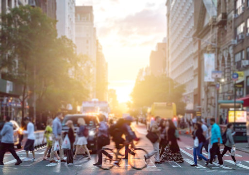 Man riding bike crosses intersection with crowds of people on 23rd Street and 6th Avenue in Manhattan with the bright sunlight background