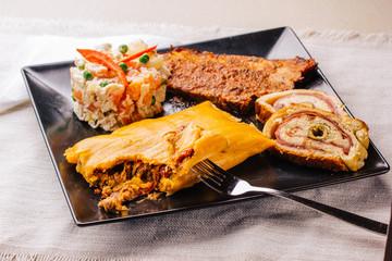 Christmas dish in Venezuela, hallaca, ham bread, salad and pork