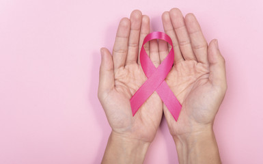 women hand holding pink ribbon breast cancer on pink background. with copy space