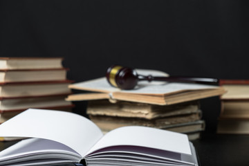 Judge gavel beside pile of books on wooden background