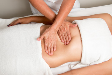 Massage Therapist Gently Massaging a Young Woman's Stomach