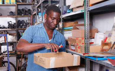 Focused African American man with box in hands choosing supplies for home renovation