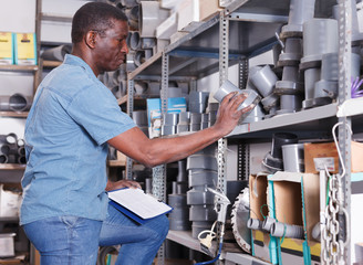 Cheerful African American male making inventory