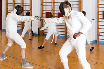 Young fencers training with coach