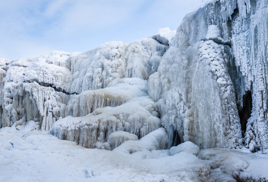 A frozen waterfall with ice in blue and white color in winter. Winter background. Jagala Waterfall, Estonia.