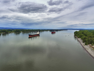 Drone Aerial of 2 cargo ships on the Columbia River on a cloudy summer day