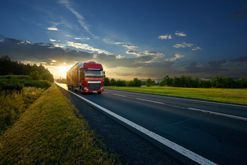 Fotobehang - Red truck arriving on the asphalt road in rural landscape in the rays of the sunset