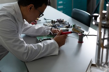 Male scientist experimenting on circuit board