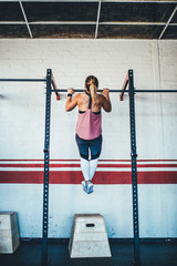 young caucasian woman doing pullups in gym