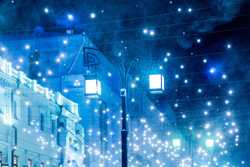 Blizzard rages around street lantern. Strong wind and snow on streets of Moscow, decorated to celebrate the New year and Christmas. Russia.