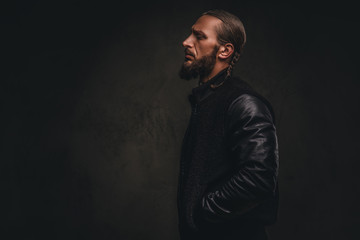 Profile of a fashionable bearded male in a black jacket. Isolated on dark textured background.