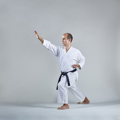 On a gray background, an adult sportsman trains a formal karate exercise