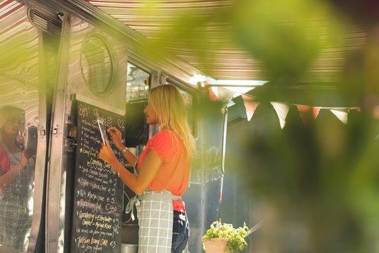 Female waitress writing menu on menu board while using digital