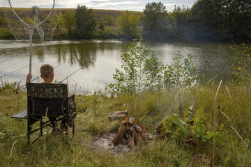 Fishing is a hobby. A bonfire on the bank of the river. Fishing on the bank of a river or a lake. Fishing and recreation in nature. Hiking. Traveling on the river bank.