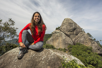 Woman sitting on rock in natural setting, Tijuca Forest, Rio de Janeiro, Brazil