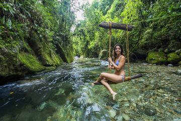 Woman on swing over river, Serrinha do Alambari Ecological Reserve in Atlantic Rainforest of Serra da Mantiqueira, Rio de Janeiro, Brazil