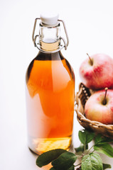 Apple vinegar in a bottle on white wooden table with apples. Rustic style.