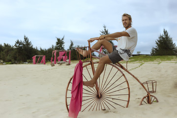 Man sitting on Penny Farthing bicycle on beach, Banda Aceh, Sumatra, Indonesia