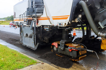 The special car with a hydrohammer removes an old paving from asphalt in the road.