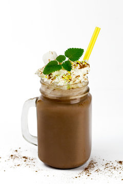 glass jar with cocoa or hot chocolate, straw, marshmallow, cinnamon, whipped cream and branch of mint isolated on white