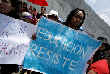 "A public sector employee holds a poster reading ""Education resists"" during a march against a tax reform proposed by the government in San Jose"