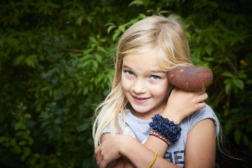 Child blong girl posing in forest and holding fresh picked mushroom (boletus). Selective focus