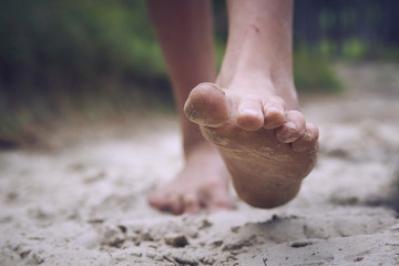 Happy barefoot child walk alone by path, explore the forest. Outdoor hiking activities.