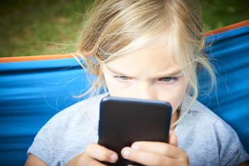 Child blond girl playing with a smart phone while lying on hammock outdoors