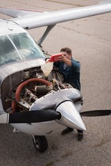 Engineer filling oil in aircraft engine