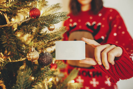 hand holding credit card close-up on background of golden beautiful christmas tree with lights in festive room. christmas shopping and sale concept. discount. black friday.
