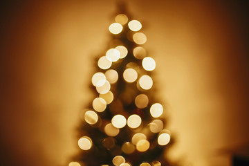 beautiful christmas tree golden lights in festive room. christmas abstract background,  blur defocused bokeh of yellow glowing decoration on christmas tree branches. decor for winter holidays