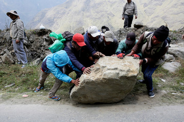 Coca growers move a stone to block a road between La Paz and Los Yungas region to protest against the government in Unduavi