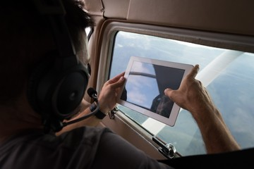 Pilot taking photos with digital table while flying