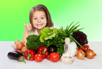 Beautiful girl with colored vegetables showing thumbs