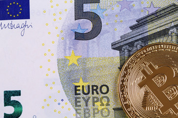 A close up image of a five Euro bill with a golden physical bitcoin