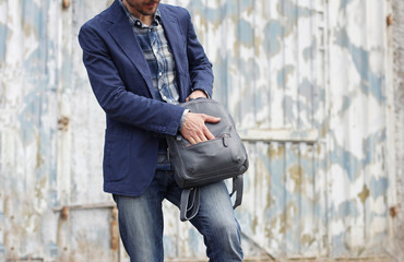Handsome man in casual wear opening zip on leather backpack. Grunge city wall on background. Trendy accessory