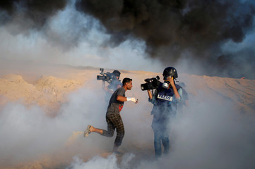 Cameramen film as a Palestinian demonstrator reacts to tear gas fired by Israeli troops during a protest calling for lifting the Israeli blockade on Gaza, on a beach near the maritime border with Israel, in the northern Gaza Strip