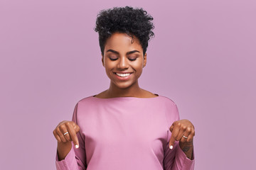 Funny surprised African American female looks with joyful eyes down and indicates as shows something, sees comic things, isolated over lavender wall. Positive amazed young woman poses in studio