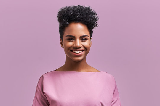Happy African American businesswoman with positive smile, has crisp dark hair, rejoices having weekend and good rest after hard working exhausting week, isolated on lavender wall